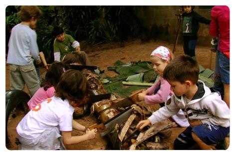 Descrição da imagem: Crianças pequenas cortam bananeira com serrote.