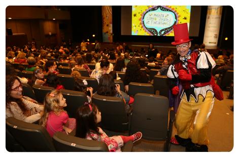 Descrição da imagem: Crianças em um cinema interagem com homem fantasiado de pierrot.