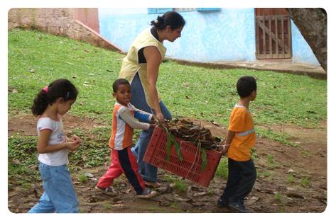 Na Associação Comunitária Monte Azul as crianças ajudam a recolher folhas secas caídas no quintal.