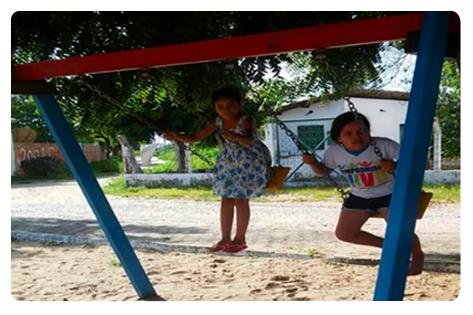 Crianças brincam no balanço.