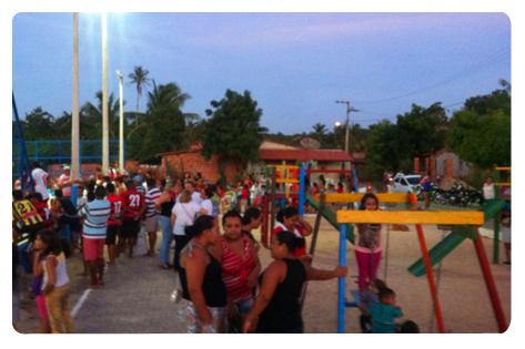 Crianças brincam em praça e muitos adultos se aglomeram em grade de quadra para ver jogo.